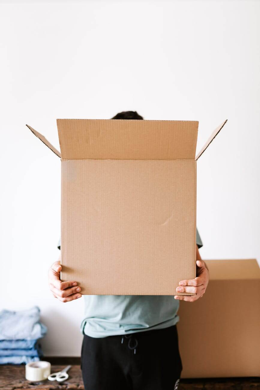 unrecognizable man with carton box in apartment